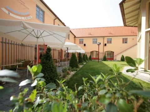 Sie sehen den Innenhof mit Sonnenschirmen, Tischen und Rasen vom JUFA Hotel Pöllau-Bio-Landerlebnis. Der Ort für erlebnisreichen Natururlaub für die ganze Familie.