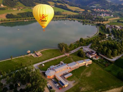 JUFA Heißluftballon direkt über dem JUFA Hotel Stubenbergsee. Der Ort für tollen Sommerurlaub an schönen Seen für die ganze Familie.