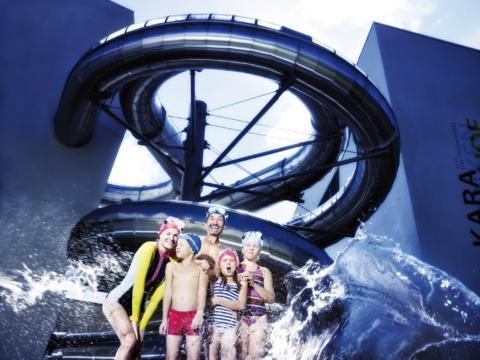 Familie steht vor der Röhrenwasserrutsche der Kärnterntherme Villach und genießt den gemeinsamen Badeausflug. JUFA Hotels bietet kinderfreundlichen und erlebnisreichen Urlaub für die ganze Familie.