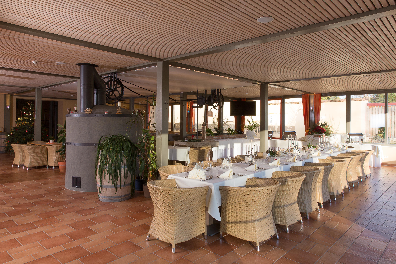 Eine gedeckte Tafel neben eines Kamins im Restaurant. Ein gemütliches Restaurant lädt zum Stärken ein im JUFA Weinviertel - Hotel in der Eselsmühle. Der Ort für erfolgreiche und kreative Seminare in abwechslungsreichen Regionen.