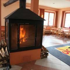 Sie sehen einen Kamin im der Lobby mit Holz im JUFA Hotel Nockberge - Almerlebnis.Der Ort für erholsamen Familienurlaub und einen unvergesslichen Winter- und Wanderurlaub.