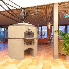 Ein Kamin im Restaurantteil mit Pflanze. Gemütliches Restaurant lädt zum Stärken ein im JUFA Weinviertel - Hotel in der Eselsmühle. Der Ort für erfolgreiche und kreative Seminare in abwechslungsreichen Regionen.