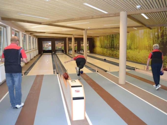Drei Personen beim Kegeln auf der Kegelbahn im JUFA Natur-Hotel Bruck. Der Ort für erlebnisreichen Natururlaub für die ganze Familie.