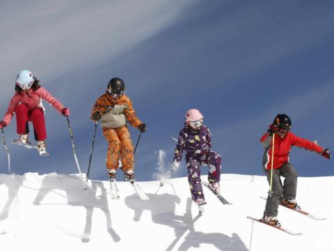 Vier Kinder springen beim Skifahren im Skigebiet Weissbriach über eine Anhöhe auf der Skipiste. JUFA Hotels bietet erholsamen Familienurlaub und einen unvergesslichen Winterurlaub.