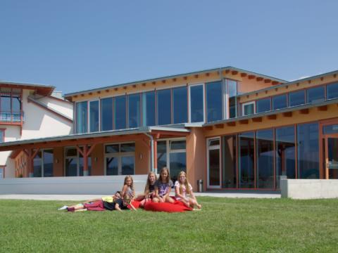 Kinder sitzen in der Wiese im Sommer vorm JUFA Hotel Knappenberg. Der Ort für erlebnisreiche und kreative Schulprojektwochen in abwechslungsreichen Regionen.