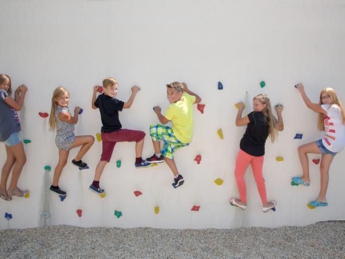 Kindergruppe beim Bouldern auf Kletterwand am JUFA Hotel Knappenberg. Der Ort für erlebnisreiche und kreative Schulprojektwochen in abwechslungsreichen Regionen.