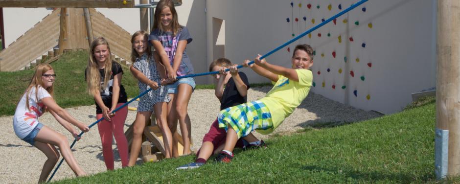 Kinder ziehen gemeinsam an einem Seil direkt auf dem Spielplatz beim JUFA Hotel Knappenberg. Der Ort für erlebnisreiche und kreative Schulprojektwochen in abwechslungsreichen Regionen.