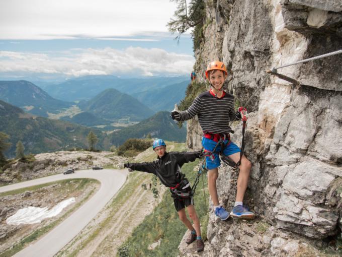 Zwei Jungs klettern am Klettersteig Sophie am Loser in Altaussee. JUFA Hotels bietet Ihnen den Ort für erlebnisreichen Natururlaub für die ganze Familie.