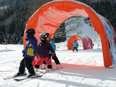 Kinder beim Skifahren auf der Krispini Tunnel-Piste in der Kinderskischaukel im Skigebiet Riesneralm. JUFA Hotels bietet erholsamen Familienurlaub und einen unvergesslichen Winterurlaub.