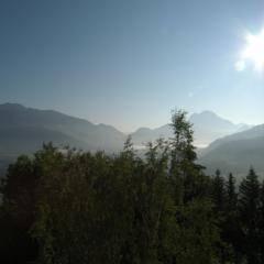 Sie sehen den Blick auf Sonne, Bäume und Berge vom JUFA Hotel Schloss Röthelstein. Der Ort für märchenhafte Hochzeiten und erfolgreiche und kreative Seminare.