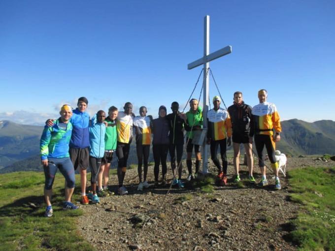 Eine Gruppe von Läufern posiert gemeinsam vor einem Gipfelkreuz. JUFA Hotels bietet Ihnen den Ort für erfolgreiches Training in ungezwungener Atmosphäre für Vereine und Teams