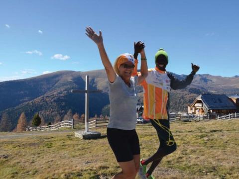 Ein Mann und eine Frau laufen händehaltend mit freudigen Gesichtern über eine Wiese mit Gipfelkreuz. JUFA Hotels bietet Ihnen den Ort für erfolgreiches Training in ungezwungener Atmosphäre für Vereine und Teams