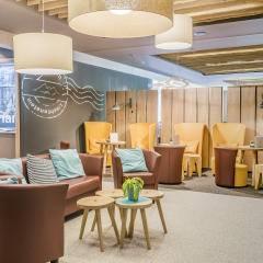 Lobby mit Tischen und Stühlen im JUFA Hotel Malbun Alpin-Resort. Der Ort für erholsamen Familienurlaub und einen unvergesslichen Winter- und Wanderurlaub.