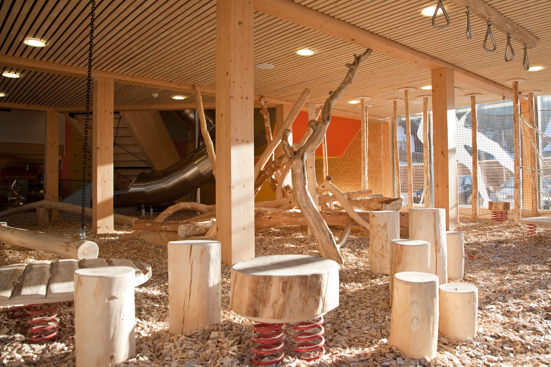 """DSie sehen einen Teil des Spielbereiches mit Holz im JUFA Hotel Montafon. Die Zeit spielend und entspannt verbringen im Kindererlebnsiwelt """"Miar gots körig"""" im JUFA Hotel Montafon.  Der Ort für erholsamen Familienurlaub und einen unvergesslichen Winter- und Wanderurlaub."""