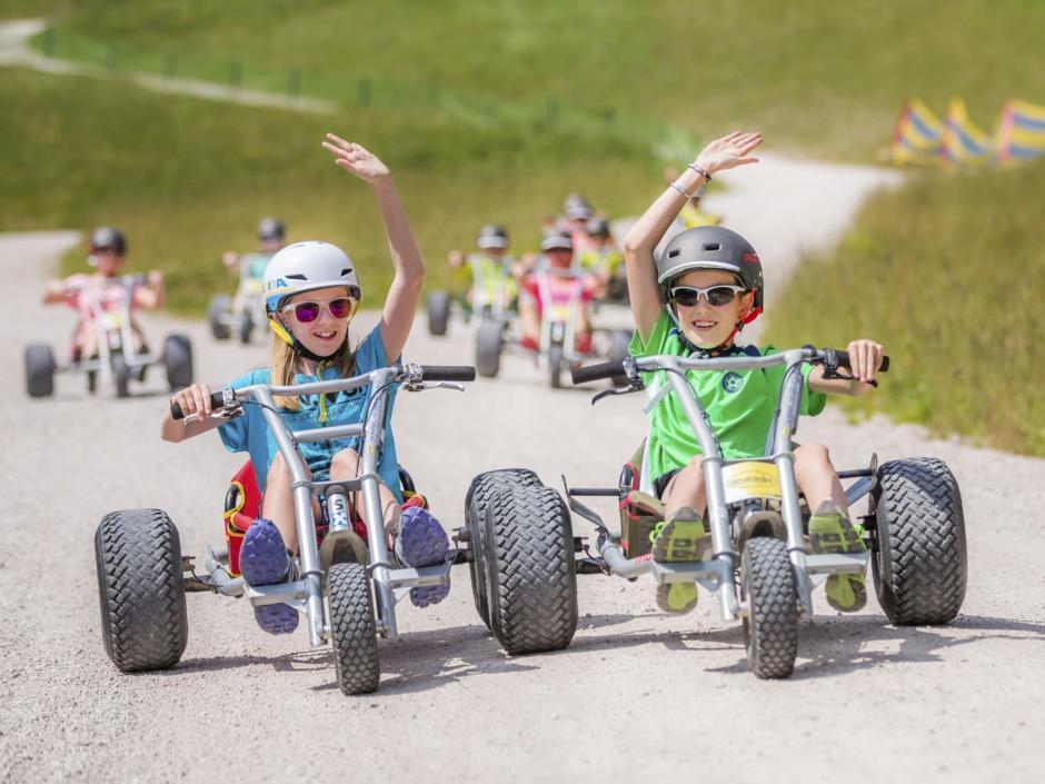 Kinder fahren auf Mountaincarts auf einem Kiesweg auf der Mariazeller Gemeindealpe in der Nähe von JUFA Hotels. Der Ort für erholsamen Familienurlaub und einen unvergesslichen Winter- und Wanderurlaub.