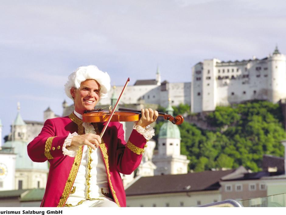 Erwachsener im Mozartkostüm spielt Geige an der Salzach. Im Hintergrund  sieht man die Festung Hohen Salzburg und die Altstadt. JUFA Hotels bietet erlebnisreichen Städtetrip für die ganze Familie und den idealen Platz für Ihr Seminar.