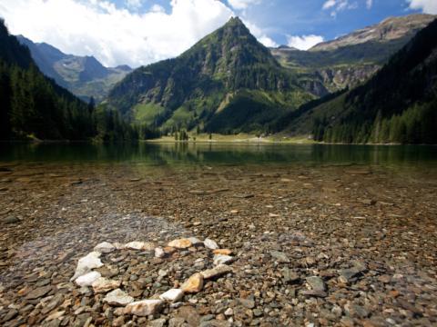 Ein Herz, gestaltet mit Steinen, am Ufer eines Sees im Naturpark Sölktäler in der Region Schladming-Dachstein. JUFA Hotels bietet Ihnen den Ort für erlebnisreichen Natururlaub für die ganze Familie.