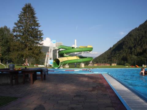 Sie sehen das Freibad in Oberwölz mit Wasserrutsche und Kindern. JUFA Hotels bietet kinderfreundlichen und erlebnisreichen Urlaub für die ganze Familie.