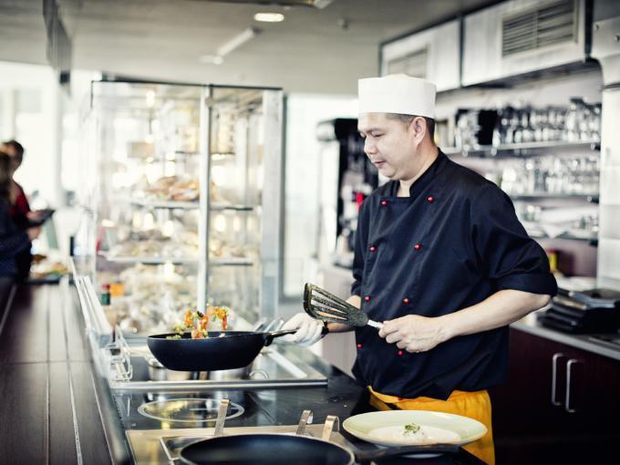 Koch beim zubereiten der Speisen in der offenen Küche im Unikum Salzburg by JUFA Hotels. JUFA Hotels bieten erholsamen Familienurlaub und einen unvergesslichen Winter- und Wanderurlaub.