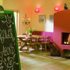 Restaurant mit Kamin, Tisch, Stühlen und einer Kreidetafel. Gemütliches Restaurant lädt zum Stärken ein im JUFA Hotel Wipptal. Der Ort für erholsamen Familienurlaub und einen unvergesslichen Winter- und Wanderurlaub.