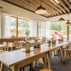 Restaurantbereich mit Fensterfront im JUFA Hotel Malbun Alpin-Resort. Der Ort für erholsamen Familienurlaub und einen unvergesslichen Winter- und Wanderurlaub.