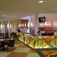 Rezeption und Hotelbar mit Cafe und Menschen im JUFA Hotel Jülich. Der Ort für kinderfreundlichen und erlebnisreichen Urlaub für die ganze Familie.