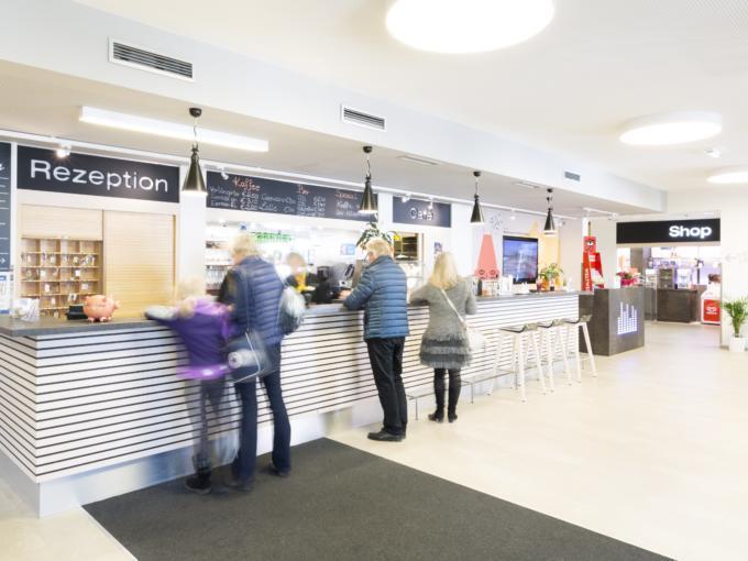Rezeption mit Blick auf JUFA Shop im JUFA Hotel Graz City. Der Ort für erlebnisreichen Städtetrip für die ganze Familie und der ideale Platz für Ihr Seminar.
