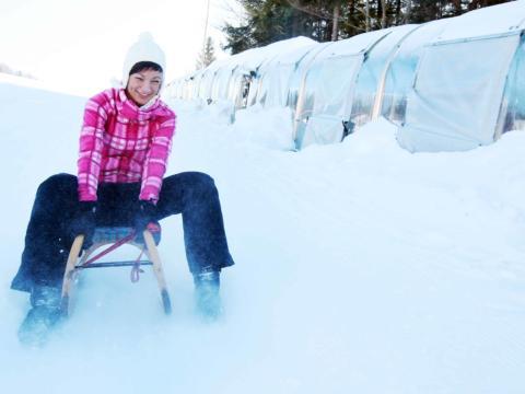 Frau beim Rodeln direkt neben dem überdachten Zauberteppich in Annaberg. JUFA Hotels bietet erholsamen Familienurlaub und einen unvergesslichen Winterurlaub.