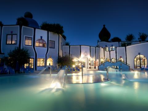 Aussenbecken der Therme Rogner Bad Blumau im Steirischem Thermenland  bei Abendstimmung. JUFA Hotels bieten erholsamen Familienurlaub und einen unvergesslichen Winter- und Wanderurlaub.