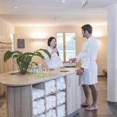 Ein Mann und eine Frau im Ruheraum mit Bar im Wellnessbereich im JUFA Hotel Malbun Alpin-Resort. Der Ort für erholsamen Familienurlaub und einen unvergesslichen Winter- und Wanderurlaub.