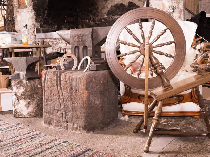 Ausstellungsraum mit Spinnrad, Amboss und Hufeisen im Schmiedemuseum Weissbriach im Gitschtal. JUFA Hotels bieten erholsamen Familienurlaub und einen unvergesslichen Winter- und Wanderurlaub.