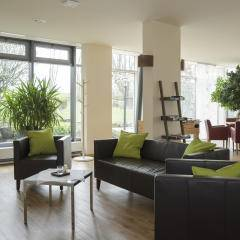 Sie sehen ein Sofa und zwei Sessel im Cafebereich vor einer Fensterfront im JUFA Hotel Wangen Sport-Resort. Der Ort für erfolgreiches Training in ungezwungener Atmosphäre für Vereine und Teams.