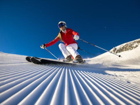 Skifahrerin fährt bei blauem Himmel die Skipiste in Altenmarkt-Zauchensee herunter in der Nähe vom JUFA Hotel Altenmarkt. Der Ort für erholsamen Familienurlaub und einen unvergesslichen Winter- und Wanderurlaub.