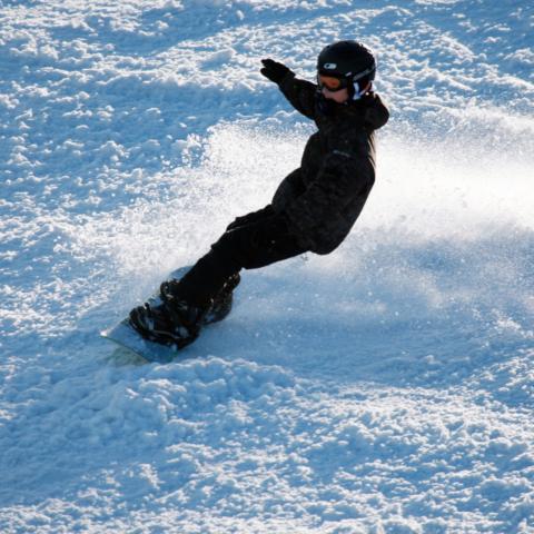 Snowboarder zieht seine Schwünge im Skigebiet Gemeindealpe im Mostviertel. JUFA Hotels bietet erholsamen Familienurlaub und einen unvergesslichen Winterurlaub.