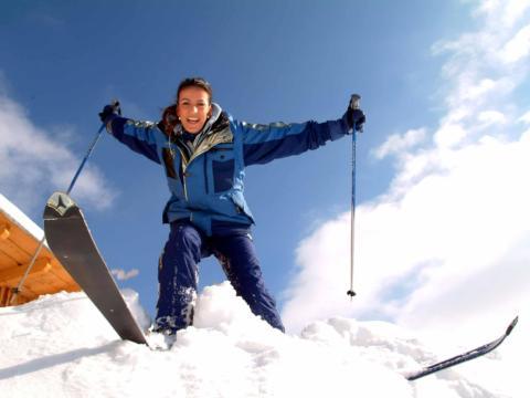 Skifahrerin im Tiefschnee im Skigebiet Präbichl bei blauem Himmel. JUFA Hotels bietet erholsamen Familienurlaub und einen unvergesslichen Winterurlaub.