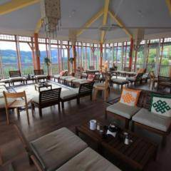 Sie sehen den Sonnengrußraum im JUFA Hotel Knappenberg mit gemütlichen Sesseln, einer Fensterfront und einem Weitblick auf die Berge. JUFA Hotel Knappenberg der Ort für einen entspannten Sommer- und Wanderurlaub für die ganze Familie.