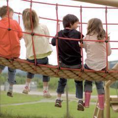Sie sehen Kinder auf einer Hängebrücke des Spielpatzes des JUFA Hotels Maria Lankowitz sitzen. Die Zeit spielend und abwechslungsreich verbringen im JUFA Hotel Maria Lankowitz. Der Ort für tollen Sommerurlaub an schönen Seen für die ganze Familie.