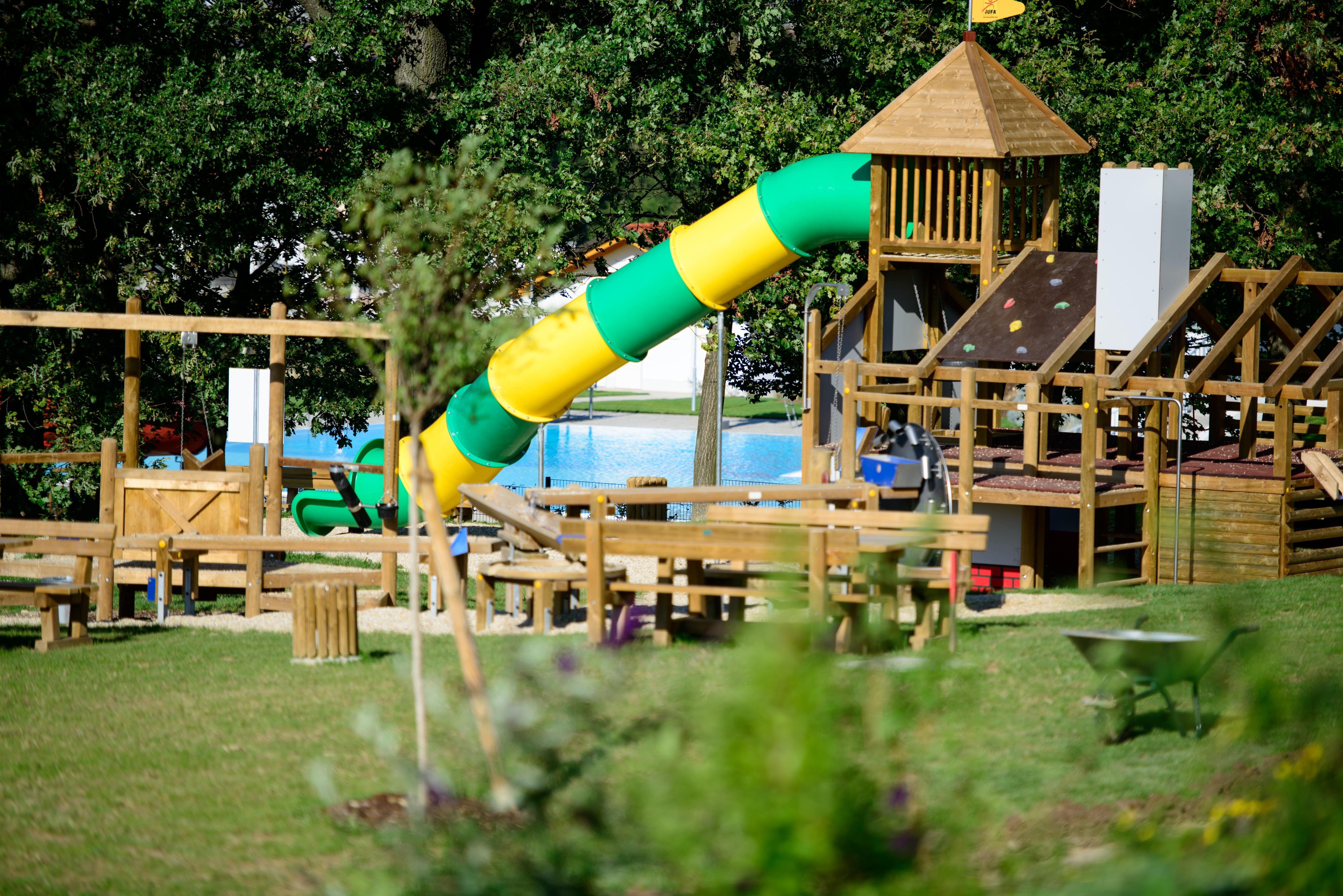 Sie sehnen den Spielplatz mit Holzgeräten und einer Rutsche und Bäumen im Hintergrund beim JUFA Hotel Neutal Landerlebnis. Die Zeit spielend und abwechslungsreich verbringen im JUFA Hotel Neutal - Landerlebnis. Der Ort für erlebnisreichen Natururlaub für die ganze Familie.