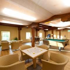 Caféhaustische mit Brettspielen und Korbsessel und Billardtisch im Hintergrund. Die Zeit spielend und abwechslungsreich verbringen im JUFA Weinviertel - Hotel in der Eselsmühle. Der Ort für erfolgreiche und kreative Seminare in abwechslungsreichen Regionen.