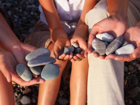 Teens sammeln Steine in der Natur. JUFA Hotels bietet erlebnisreiche und kreative Schulprojektwochen in abwechslungsreichen Regionen.