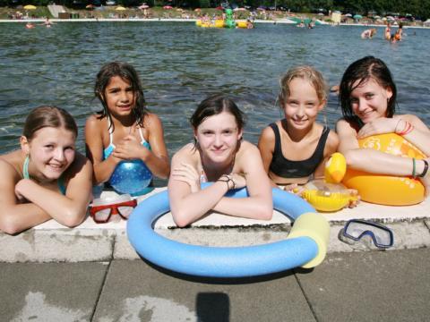 Teens am Beckenrand im Freibad mit Schwimmutensilien im Sommer. JUFA Hotels bietet erlebnisreiche Feriencamps in den Bereichen Sport, Gesundheit, Bildung und Sprachen.