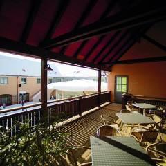 Sie sehen die Terrasse mit Tischen und Blick in den Innenhof im JUFA Hotel Pöllau-Bio-Landerlebnis.Der Ort für erlebnisreichen Natururlaub für die ganze Familie.