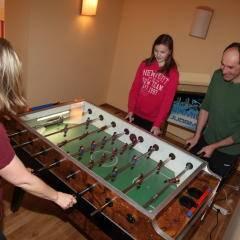 Familie beim Tischfußballspielen im JUFA Hotel Nockberge Almerlebnis. Der Ort für erholsamen Familienurlaub und einen unvergesslichen Winter- und Wanderurlaub.