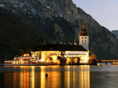 Ein Schiff der Traunseeschifffahrt fährt am Seeschloss Ort in Gmunden vorbei. JUFA Hotels bietet erholsamen Familienurlaub und einen unvergesslichen Winterurlaub.