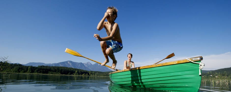 Junge springt vom Ruderboot in den Turnersee im Sommer. JUFA Hotels bietet tollen Sommerurlaub an schönen Seen für die ganze Familie.