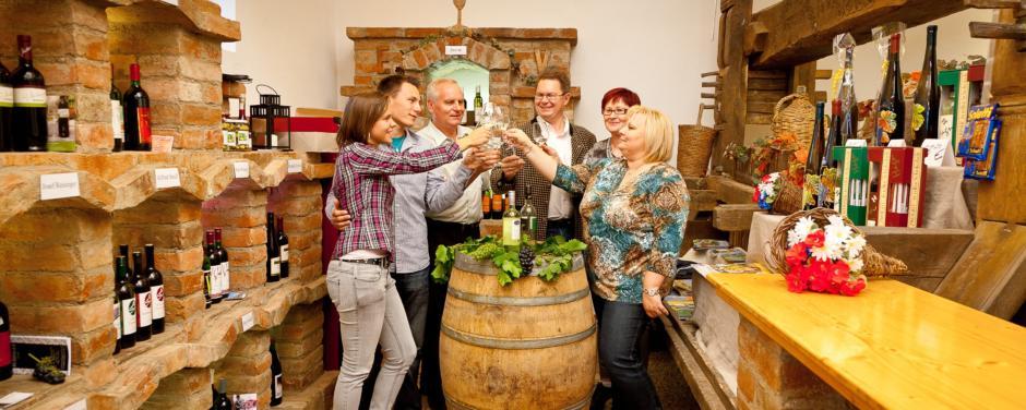 Verkaufsraum für Weine mit einem alten Weinfass als Tisch mit Menschen.Weinerleben in unterschiedlichen Facetten im JUFA Weinviertel - Hotel in der Eselsmühle. Der Ort für erfolgreiche und kreative Seminare in abwechslungsreichen Regionen.
