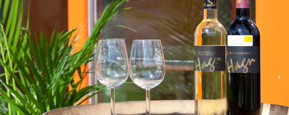 Zwei Weinflaschen mit zwei Gläsern auf einem alten Weinfass. Die vielen Kleinigkeiten machen Ihren Urlaub zu einem besonderen Erlebnis im JUFA Weinviertel - Hotel in der Eselsmühle. Der Ort für erfolgreiche und kreative Seminare in abwechslungsreichen Regionen.
