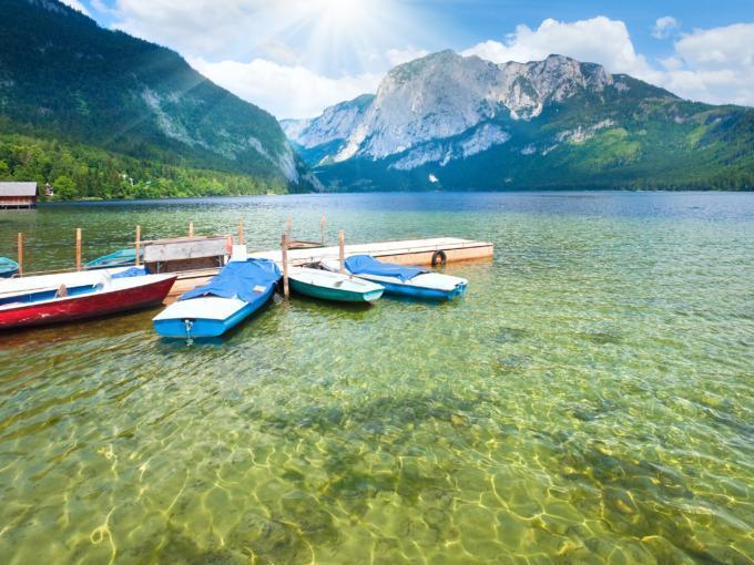Boote liegen am Steg am Ufer des Altausseer Sees. JUFA Hotels bietet tollen Sommerurlaub an schönen Seen für die ganze Familie.