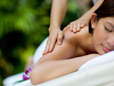 Eine Frau auf einer Massageliege genießt eine entspannende Rückenmassage. JUFA Hotels bietet erholsamen Thermen- und Badespass für die ganze Familie.