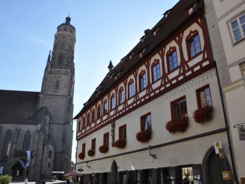 Ein altes Haus und eine Kirche als Baudenkmäler in Nördlingen. JUFA Hotels bietet erholsamen Familienurlaub und einen unvergesslichen Winter- und Wanderurlaub.